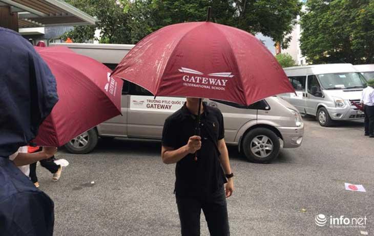 Các nhân viên của nhà trường tìm mọi cách che chắn nhằm ngăn cản các phóng viên chụp hình ông Doãn Quý Phiến trong xe.